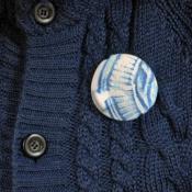 broche met handbedrukt dessin op textiel